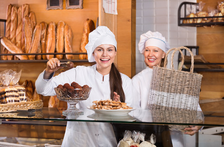 patty cake: Hospitable happy women with delicious cream pies at a bakery display