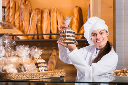 Friendly young female staff selling fresh pastry and baguettes in local bakery
