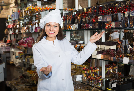 shopgirl: Happy smiling young shopgirl posing with different delicious chocolate and confectionery at display