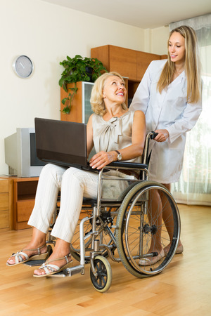 incapacitated: Young social worker and disabled mature woman on chair with laptop. Focus on woman