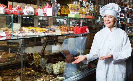 seller: Elderly cheerful positive seller with dark and white chocolates confectionery at display