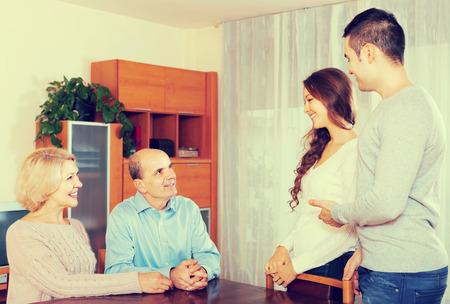 introducing: Adult smiling daughter introducing her boyfriend to parents indoor Stock Photo