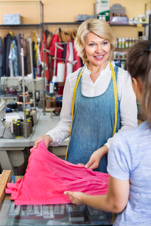 customer tailor: Cheerful mature woman tailor taking order from customer in sewing workshop Stock Photo