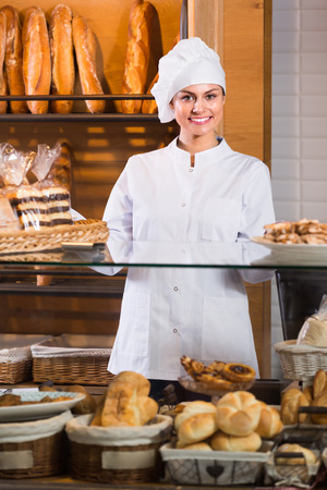 filled roll: Smiling young baker  selling fresh pastry and baguettes in local bakery Stock Photo