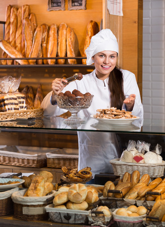 shopgirl: portrait of  shopgirl working in bakery with bread and different pastry