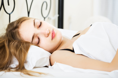 early twenties: Charming brunette girl sleeping on white pillow in bed