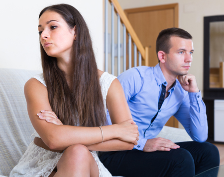 Sad young couple sulking on each other during quarrel at home Stock Photo