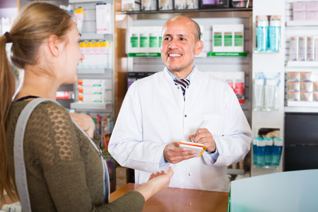 farmacy: Experienced pharmacist counseling european female customer in modern farmacy