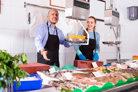 shopgirl: Shopgirl and positive salesman posing near display with chilled fish Stock Photo