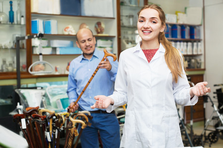 Mature man asking friendly positive  female doctor about walking sticks in store