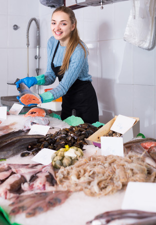fishery products: Pretty spanish  shopgirl with apron offering fresh fish in shop