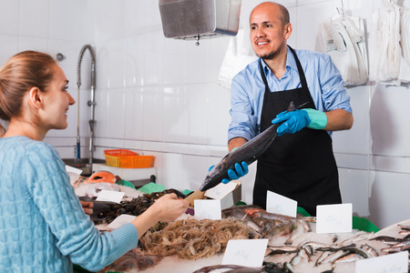 Pleasant friendly seller helping female customer to choose chilled fish