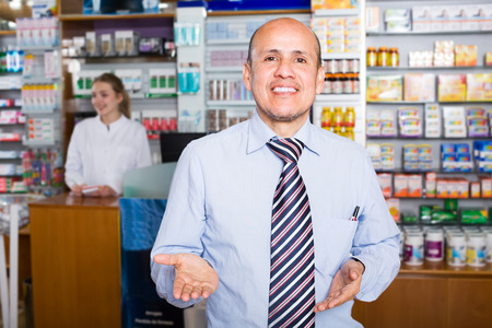 farmacy: portrait of experienced pharmacist counseling female customer in modern farmacy