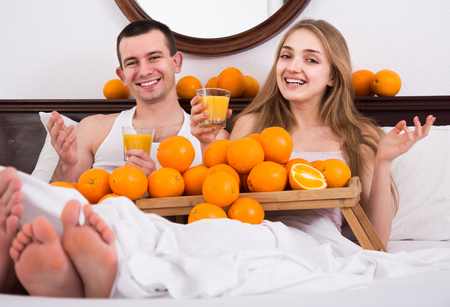 russian man: happy russian man and girlfriend drinking squeezed orange juice in bed