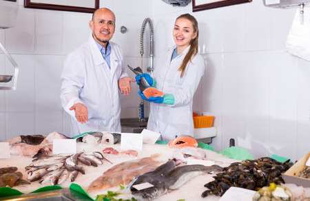 Cheerful smiling shopgirl and salesman offering cooled fish. Focus on man