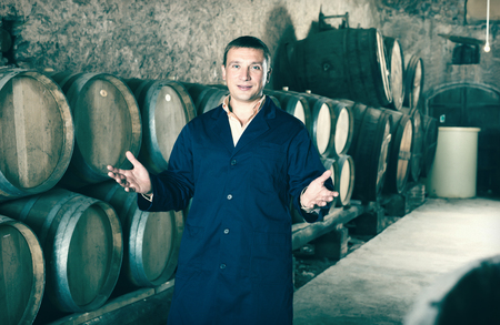 laboratorian: Positive worker of winery posing with wine barrels in cellar