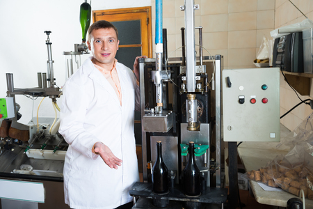 laboratorian: positive male assembly line operator working in modern wine factory