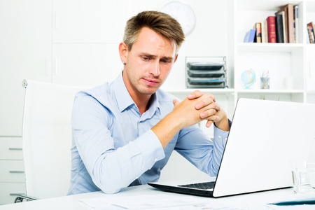 depressive: Depressive adult man sitting at working desk with laptop and having work troubles in office