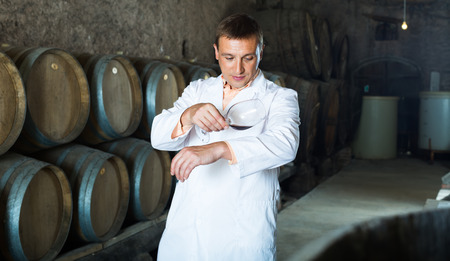 factory sommelier in white robe checking quality of red wine in cellar with barrels