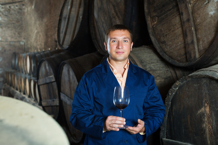 ageing process: Serioius young male in robe keeping ageing process of wine under control Stock Photo