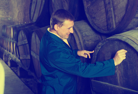 laboratorian: Smiling young man in robe checking ageing barrel process of wine Stock Photo