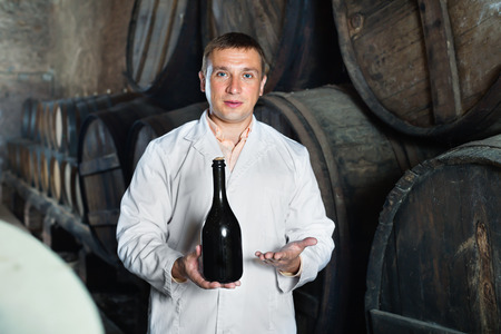 laboratorian: Wine house technician holding bottle near wooden barrels in storage