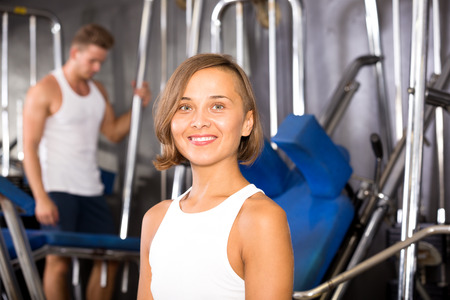 Portrait of glad young woman sitting on bench between exercises in gym