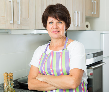 glad: Portrait of glad mature woman housewife standing at kitchen indoors