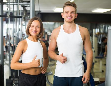 giovane uomo e donna di fitness sorridenti allenatori che prendono pausa durante l'allenamento in palestra al chiuso