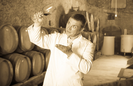 Positive taster posing with glass of wine in winery cellar