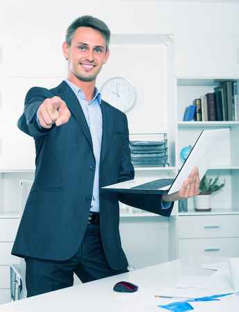 trustworthy: positive business male employee standing with laptop in hands in firm office