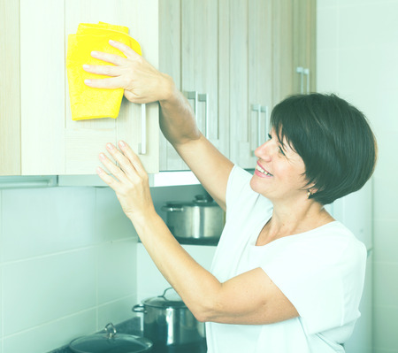 glad: glad retiree woman cleaning surfaces at home using duster and household chemicals Stock Photo