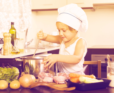 Cute baby girl in chef's hat cooking food at home kitchen
