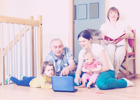 three generations of women: Happy multigeneration family together with notebook at floor at home