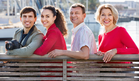 Happy pleasant  family of four enjoying the sunny spring day together near sea Stock Photo