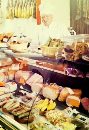 carniceria: Alegre vendedor macho maduro posando con wursts en una carnicería
