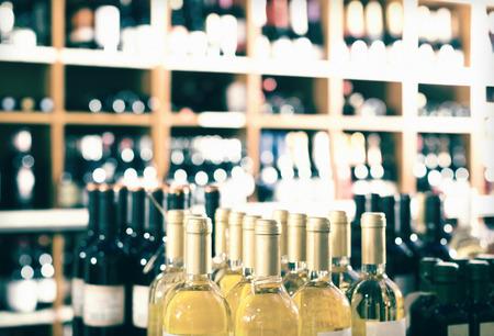 tomando refresco: Ver en estantes de la tienda de vinos con gran variedad de botellas de vino