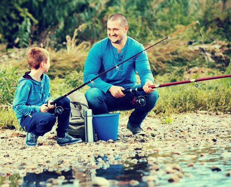 manhood: Portrait of  father and smiling son fishing with rods in summer day Stock Photo