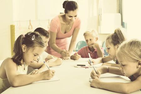 diligente: niños diligentes Glad aprender a escribir en la lección en la clase de la escuela primaria