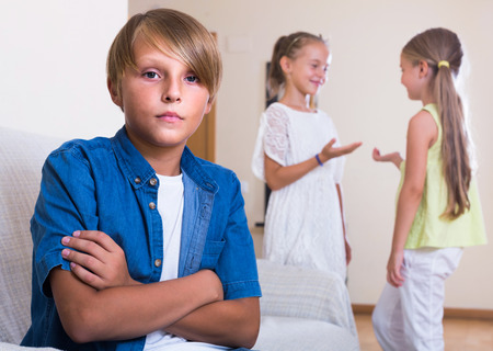 morose: Two little european girls talking and sulky boy sitting separately at home. Focus on boy
