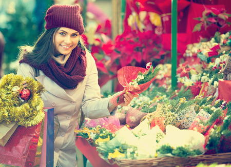 overspending: Pretty  girl buying floral compositions at Christmas fair Stock Photo