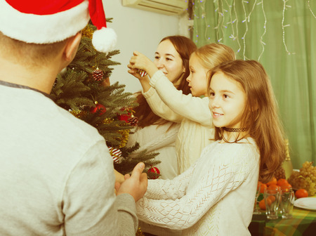 four happy people decorating christmas tree at home stock photo 65665200 - People Decorating A Christmas Tree