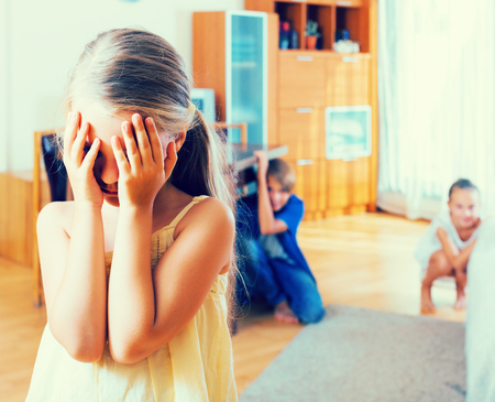romp: Teenage boy with little sisters playing hide-and-go-seek indoors
