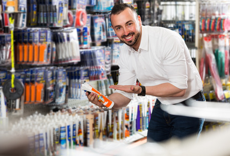 sealant: cheerful glad man picking sealing component in household shop Stock Photo