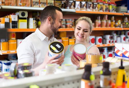 russian man: young russian man and woman picking paint tin together in household shop Stock Photo