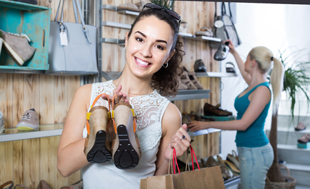 smiling european girl holding a picked pair of shoes in the boutique