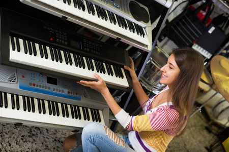 synthesiser: Happy adult girl selecting control keyboard for synthesiser in shop Stock Photo