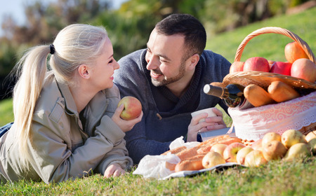 Loving smiling couple chatting as having picnic in sunny day