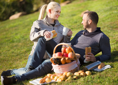 sandwitch: Loving happy young couple chatting as having picnic in sunny day