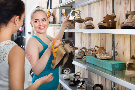 25 35: Ttwo glad young women selecting a shoes and chatting among the shelves